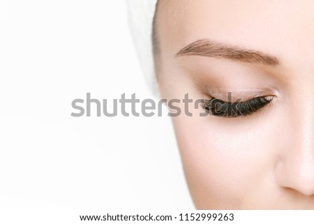 Eyelash extension procedure. Beautiful woman with long eyelashes. Facial treatment. Cosmetology, beauty skin care and spa concept. Isolated on white background. Permanent makeup. Microblading brow.