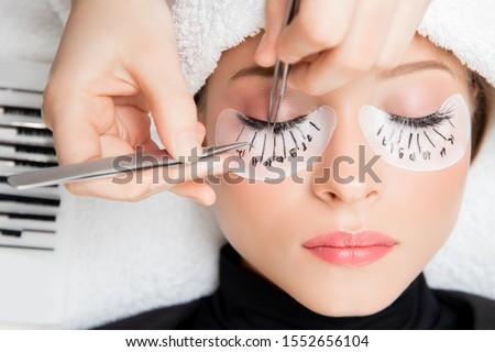 Eyelash extension procedure. Master tweezers fake long lashes beautiful female eyes. Stockfoto ©