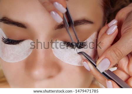 Eyelash Extension Procedure. Woman Eye with Long Blue Eyelashes. Close up, selective focus. Stockfoto ©