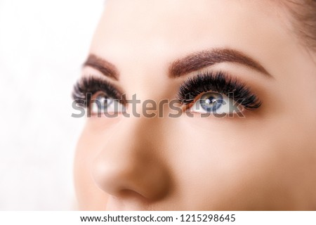 Eyelash Extension Procedure. Woman Eye with Long Eyelashes. Close up, selective focus. Hollywood, russian volume