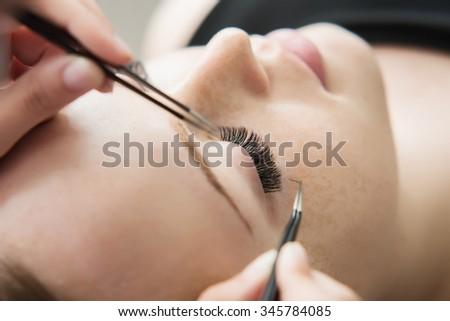 Eyelash Extension Procedure.  Woman Eye with Long Eyelashes. Lashes. Close up, selected focus. Shallow DOF.