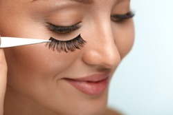 Eyelashes. Beautiful Woman Applying False Eyelashes With Tweezers. Closeup Of Young Female Model Face With Professional Facial Makeup, Smooth Skin And Long Black Thick Eye Lashes. High Resolution