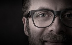 Eyes and glasses - happy smiling bearded caucasian man's face close up (macro). Successful businessman portrait on black background, dark moody light. Layout with free text (copy) space.