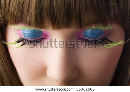 eyes close up of beautiful young woman with green eyelashes and vibrant color