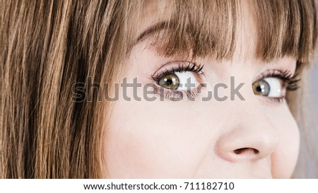 Eyes close up of woman having surprised face expression seeing something surprising or shocking. #711182710