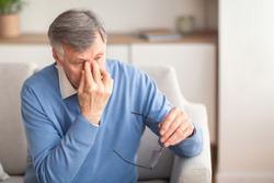 Eyes Fatigue. Senior Man Massaging Nosebridge Sitting On Sofa At Home. Selective Focus, Free Space