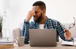 Eyes Fatigue. Tired Black Guy Massaging Nosebridge Holding Eyeglasses After Work On Laptop Computer Sitting At Workplace In Modern Office. Poor Eyesight, Glaucoma Problem. Selective Focus