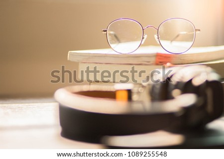 Eyes glasses on books with headphone at room in sunlight.