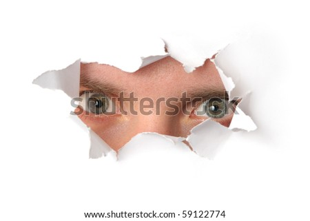 Eyes looking through a hole in a paper