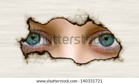 Eyes looking through a hole in paper