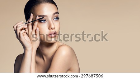 Eyes make-up. Photos of appealing brunette girl applying mascara on beige background