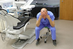 Eyes problem.Tired mature dentist having short break for regeneration after long working hours in his office