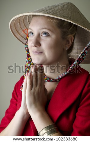 Eyes towards asia. Attractive young woman wearing asian hat and red jacket with hands in prayer position looking to the east
