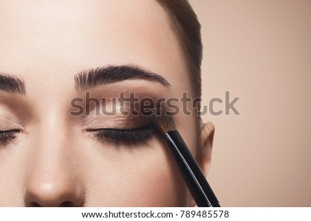 Eyeshadow applying, makeup for eyes closeup. Female model face with fashion make-up, beauty concept