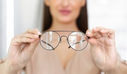 Eyesight And Vision Concept. Closeup of unrecognizable woman showing new eyeglasses to camera, standing at optics store, blurred background, selective focus on eyewear. Lady offering specs