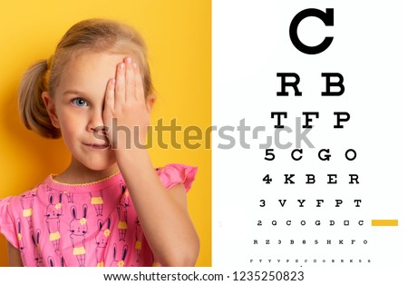 eyesight check. girl covering one eye with hand. eyesight check and health examinations. Kid closing one eye with hand against alphabetical out of focus eye test chart in background.