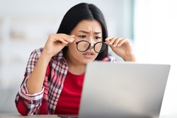 Eyesight Problems. Young Asian Female Taking Off Glasses While Looking At Laptop Screen At Home, Korean Freelancer Woman Suffering Bad Vision While Working Remotely On Computer, Closeup Shot