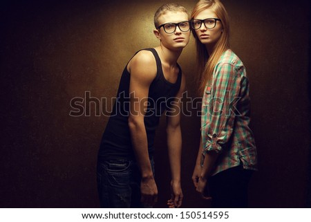 Eyewear concept. Portrait of gorgeous red-haired (ginger) fashion twins in casual shirts wearing trendy glasses and posing over golden background together. Hipster style. Copy-space. Studio shot