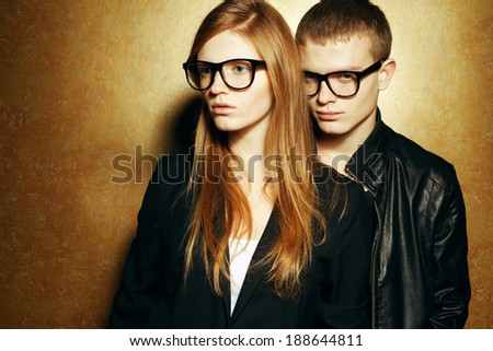 Eyewear concept. Portrait of gorgeous red-haired twins in black clothes wearing trendy glasses and posing over golden background together. Perfect hair & skin. Hipster style. Copy-space. Studio shot