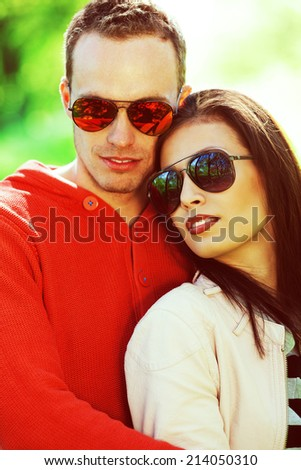 Eyewear concept. Smiling young woman and her boyfriend in trendy sunglasses posing in the park. Stylish casual clothing. White shiny smiles. Spring (autumn) sunny weather. Close up. Outdoor shot
