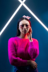 Eyewear fashion. Neon portrait. Cyberpunk futuristic vogue. Glamour Asian girl in stylish sunglasses magenta pink color sweater with white LED lamp light isolated on dark blue.