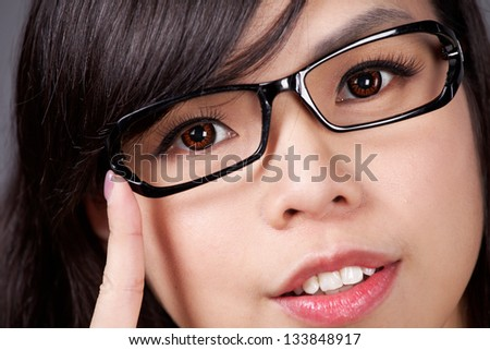 Eyewear glasses woman closeup portrait. Woman wearing glasses holding frame in close-up. Beautiful young mixed race Caucasian / Asian Chinese female model - stock photo