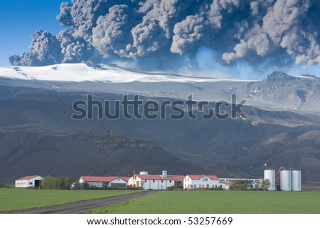 Eyjafjallajokull in Iceland erupting, ash plume against blue sky above the farm Thorvaldseyri, green fields in the foreground