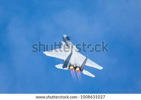 F-15 Eagle in a very close view, with afterburners on and clouds in the background