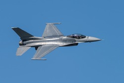 F-16 Fighting Falcon Silhouette in Clear Blue Sky with Fighter Pilot Visible