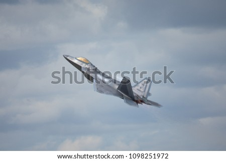 F-22 Raptor in a high G maneuver, with condensation trails forming  above the wing and the hot jet stream visible against the clouds