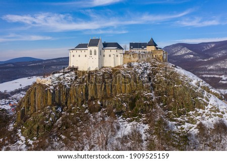 Füzér, Hungary - Aerial view of the famous castle of Fuzer built on a volcanic hill named Nagy-Milic. Zemplen mountains at the background. Winter landscape. Hungarian name is Füzér vára. Stock fotó ©