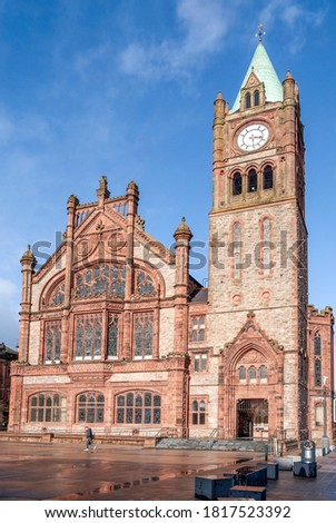 Façade of Guildhall in Derry/Londonderry, Northern Ireland, built in the 19th century with red bricks and the clock tower, meeting place of the local city council.