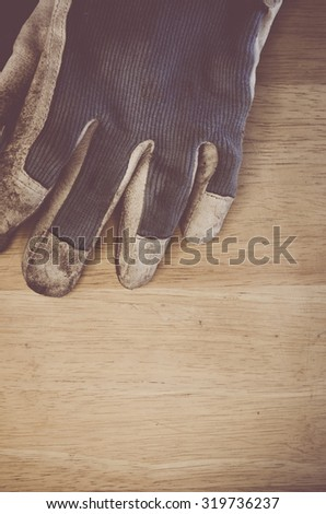 fabric and leather worn out work gloves on a wood background - vintage look processing