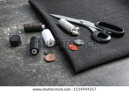 Fabric and sewing accessories on dark background #1114944317