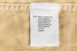 Fabric composition clothes label on beige cotton as a background