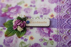 Fabric covered weddig scrapbook album with purple lace, flowers and inscription Handmade. Soft focused close up shot.