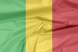 Fabric flag of Mali. Crease of Malian flag background, A vertical tricolor of green gold and red.
