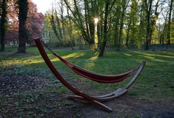 fabric hammock net in designer hanging shape half moon crescent in park at sunrise springtime green leaves forest and red seduces lie down