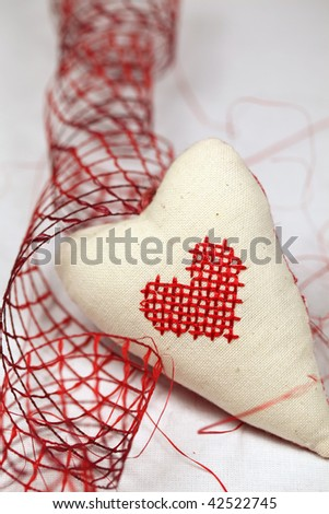 Fabric heart with embroidered little heart and red ribbon. Shallow DOF, copy space