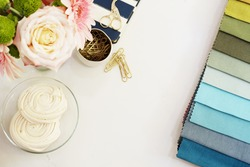 Fabric samples on the table. The designer workplace concept. Freelance fashion comfortable femininity workspace in flat lay style with flowers on marble background. Top view, bright, pink and gold