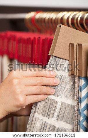 Fabric shop. Woman\'s hands checking the material quality of some fabric