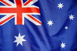 Fabric texture flag of Australia. Flag of Australia waving in the wind. Australia flag is depicted on a sports cloth fabric with many folds. Sport team banner.