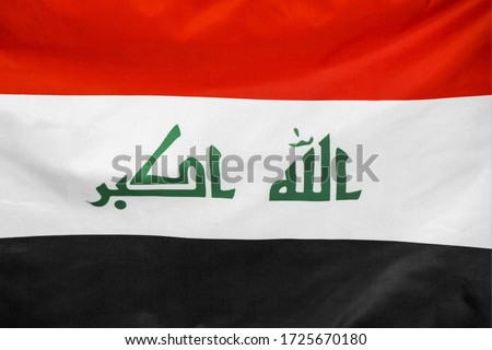 Fabric texture flag of Iraq. Flag of Iraq waving in the wind. Iraq flag is depicted on a sports cloth fabric with many folds. Sport team banner.
