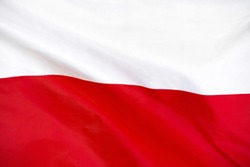Fabric texture flag of Poland. Flag of Poland waving in the wind. Poland flag is depicted on a sports cloth fabric with many folds. Sport team banner.