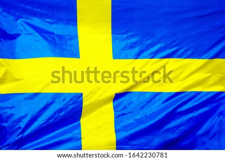 Fabric texture flag of Sweden. Flag of Sweden waving in the wind. Sweden flag is depicted on a sports cloth fabric with many folds. Sport team banner.