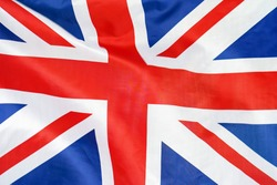 Fabric texture flag of United Kingdom. Flag of United Kingdomwaving in the wind. UK flag is depicted on a sports cloth fabric with many folds. Sport team banner.