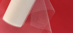 Fabric - white mesh in a roll on a red background. Nylon tape for tying bows on hair. A skein of tulle fabric. Copy space