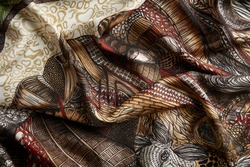 Fabric with geometric prints in orange and red colors prevailing. Corrugated fabric in closeup