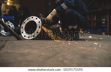 Fabric worker in protective uniform cutting metal pipe on the work table with an electric grinder in the industrial workshop. #1019175595