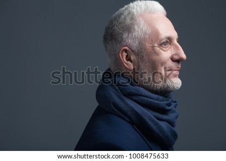 Fabulous at any age concept. Close up portrait of 60-year-old man wearing trendy accessory, standing over gray background. Street style. Copy-space. Studio shot #1008475633